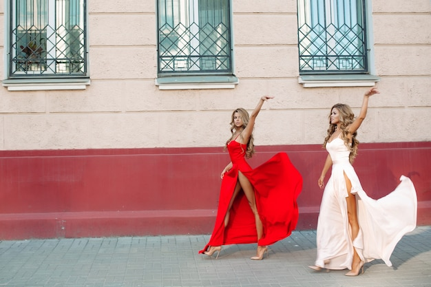 Donne sicure e alla moda che si alzano per i suoi eleganti abiti da sera Foto Premium