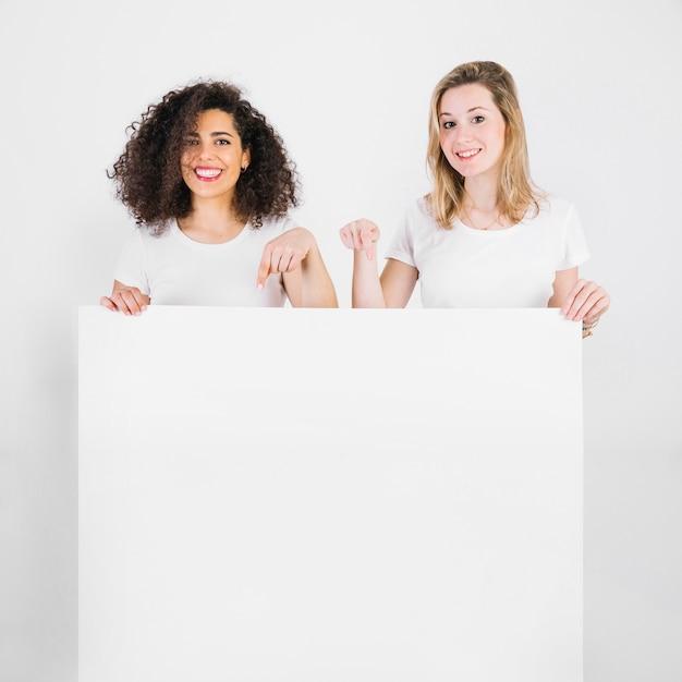 Donne sorridenti che indicano sul manifesto in bianco Foto Gratuite