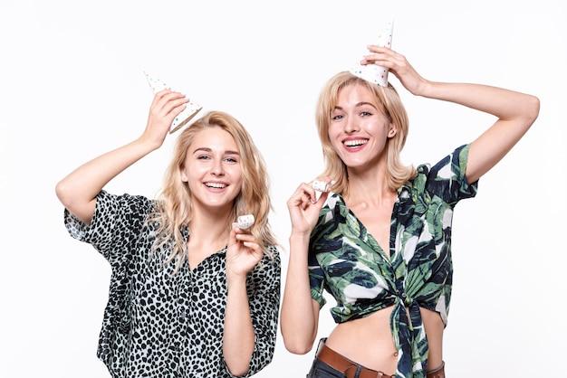 Donne sorridenti che sollevano i loro cappelli del partito Foto Gratuite