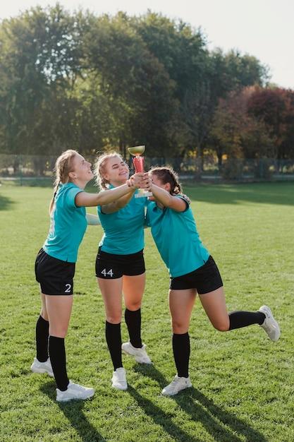 Donne sorridenti che tengono un trofeo di calcio Foto Gratuite
