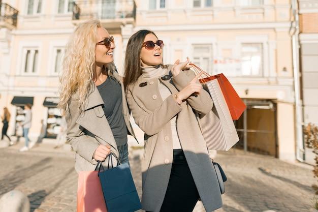 Donne sorridenti su una strada cittadina con borse della spesa Foto Premium