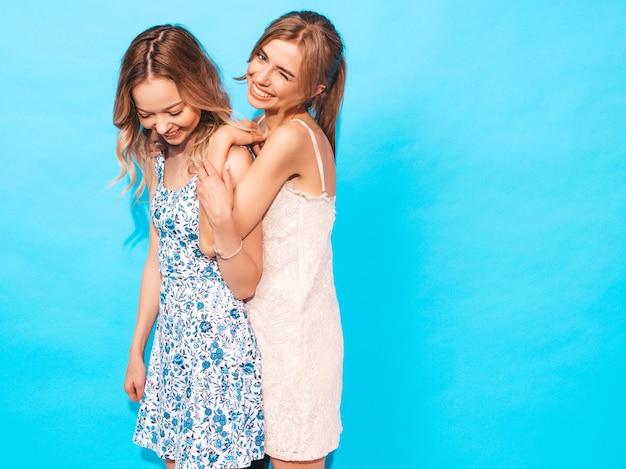 Donne spensierate sexy che posano vicino alla parete blu. divertirsi e abbracciarsi Foto Gratuite
