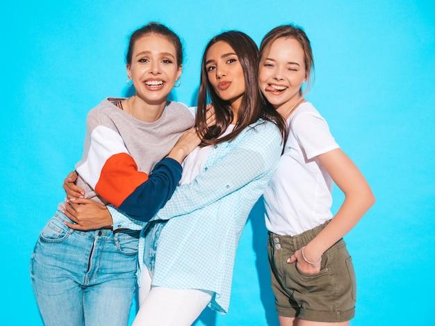 Donne spensierate sexy che posano vicino alla parete blu in studio. modelli positivi che si divertono e si abbracciano Foto Gratuite