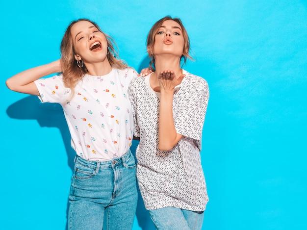 Donne spensierate sexy che posano vicino alla parete blu. modelle positive che si divertono e mostrano una smorfia divertente Foto Gratuite