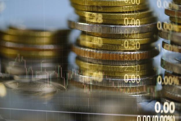 Doppia esposizione della pila della moneta con lo schermo del mercato azionario e il bastone di candela Foto Premium
