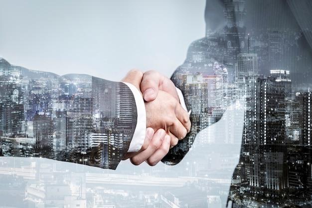 Doppia esposizione della stretta di mano della partnership commerciale e della città moderna, saluto d'affari di successo o accordo dopo un accordo perfetto Foto Premium