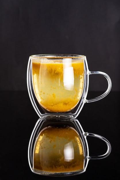 Doppia tazza di vetro con tè sano fatto in casa all'olivello spinoso sulla superficie nera Foto Premium
