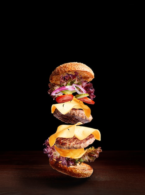 Doppio cheeseburger su una superficie di legno con uno sfondo scuro e spazio per il testo Foto Premium