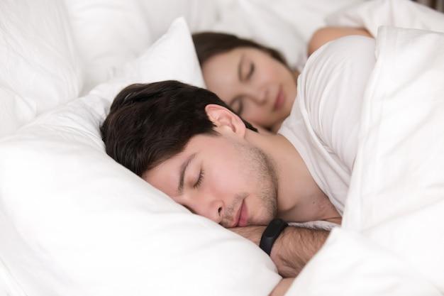 Dormire giovane coppia a letto, uomo che indossa smart watch tracker Foto Gratuite
