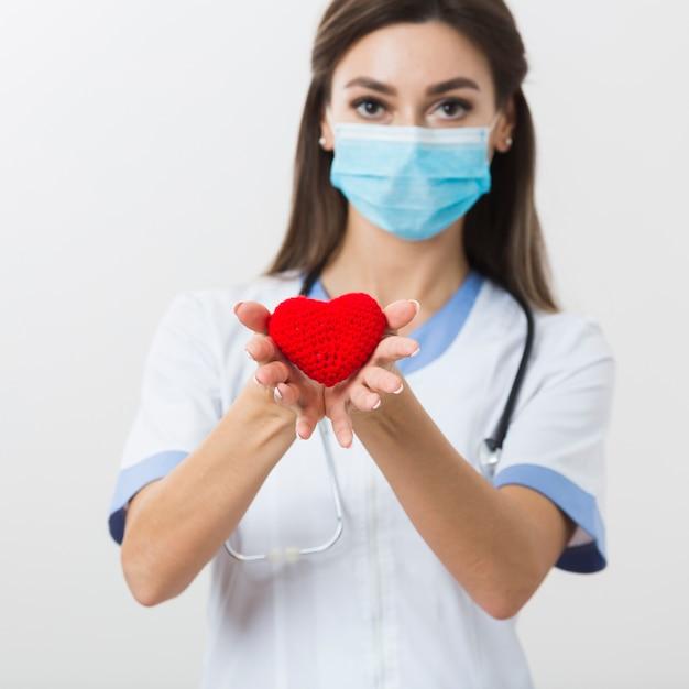 Dottoressa che offre un cuore di peluche Foto Gratuite