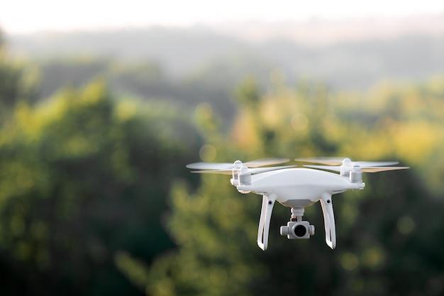 Drone di quadcopter che vola con una macchina fotografica sopra un lago. Foto Premium