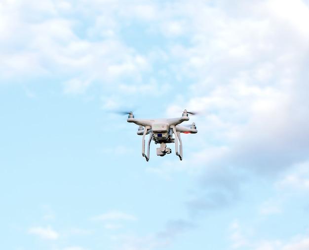 Drone quadcopter con la fotocamera contro il cielo blu Foto Premium