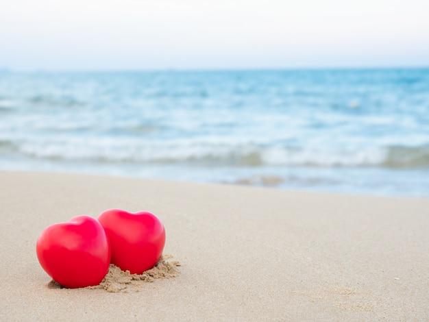 Due a forma di cuore messo sulla sabbia in spiaggia e mare blu sfocato sfondo Foto Premium