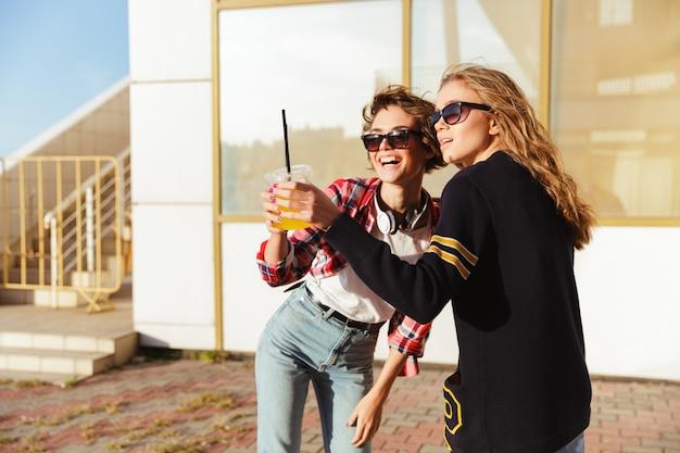 Due adolescenti felici in occhiali da sole che tostano Foto Gratuite