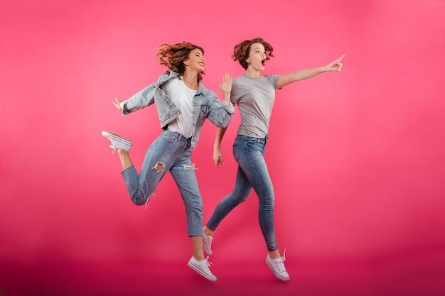 Due amiche emozionanti che saltano e che indicano. Foto Gratuite