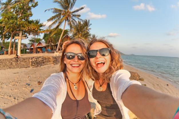 Due amiche felici che fanno selfie sulla costa del mare tropicale Foto Premium