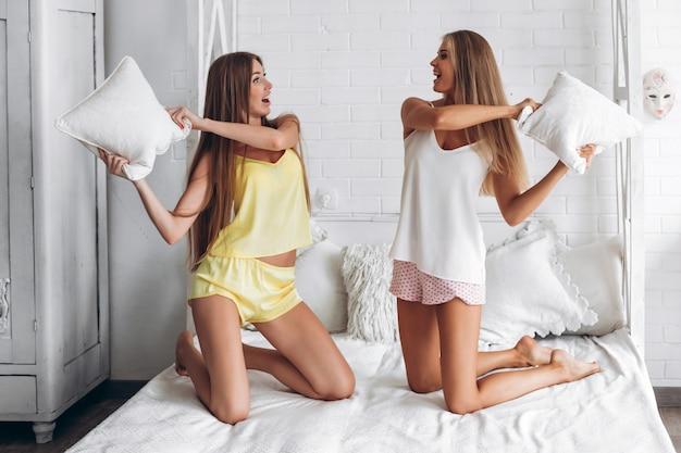 Due amiche in biancheria intima che hanno lotta con i cuscini in camera da letto Foto Premium