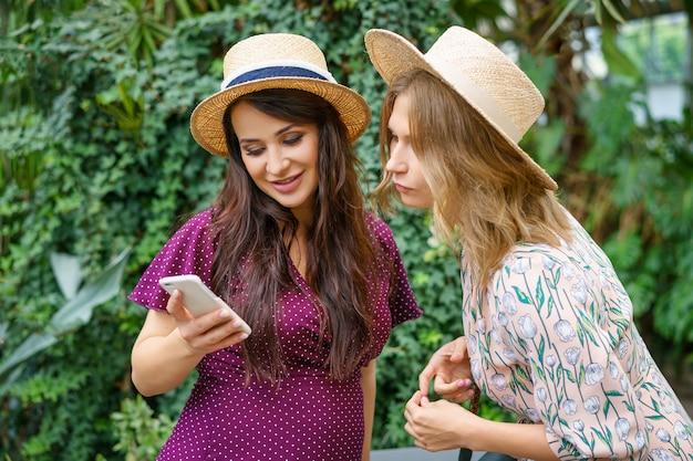Due amici allegri guardano il telefono, rendono naturali i cappelli selfie su uno sfondo verde. Foto Premium
