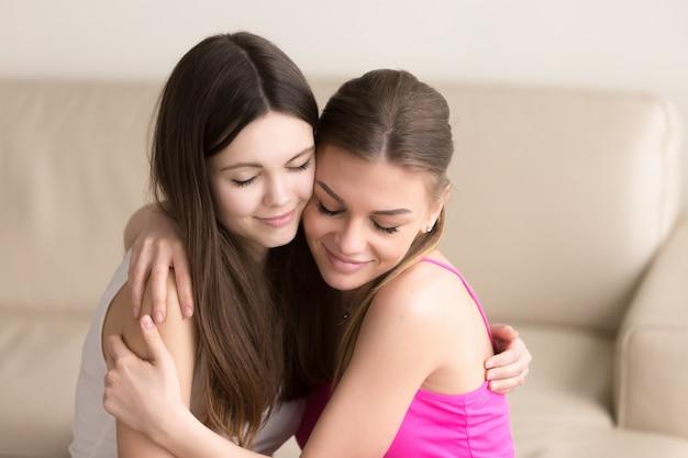 Due amici delle giovani donne che abbracciano delicatamente sul sofà Foto Gratuite
