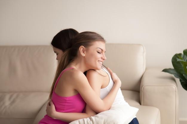 Due amici delle giovani donne che abbracciano sul sofà Foto Gratuite