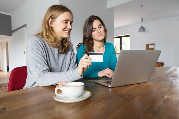 Due amici femminili felici che per mezzo del computer portatile Foto Gratuite