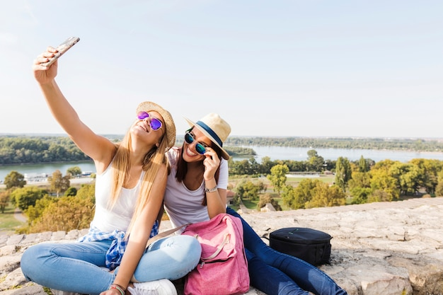 Due amici femminili felici che prendono selfie sul cellulare Foto Gratuite