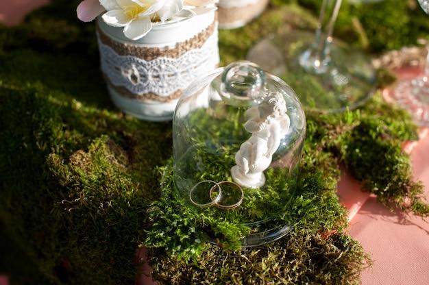 Due anelli di nozze d'oro su un tavolo sotto un bicchiere di vetro Foto Premium