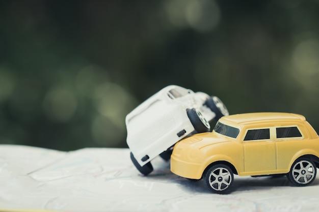 Due auto in miniatura arresto di collisione su strada, auto auto giocattoli rotti sulla mappa della città Foto Premium