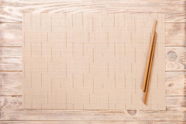Due bacchette sushi con stuoia di bambù marrone vuota o piastra di legno Foto Premium