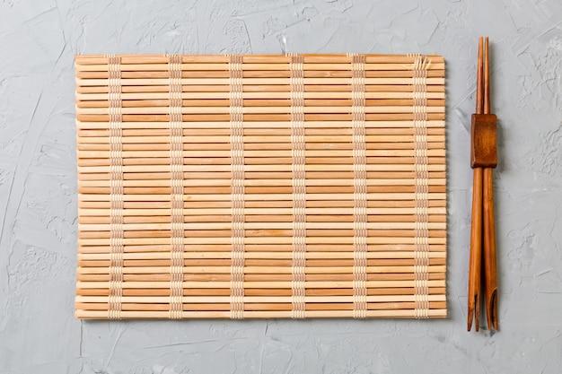 Due bacchette sushi con stuoia di bambù vuota o piastra di legno Foto Premium