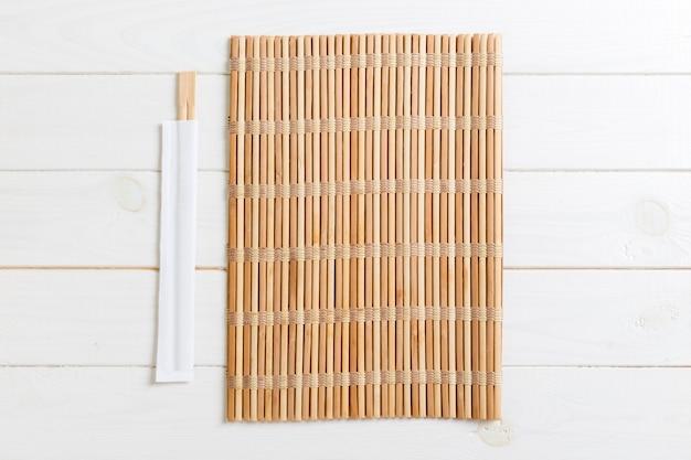 Due bacchette sushi con stuoia di bambù vuota o piatto di legno su legno Foto Premium