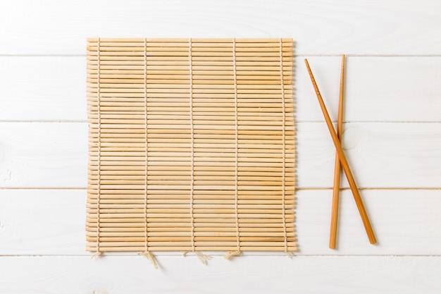 Due bacchette sushi con stuoia di bambù vuota su legno Foto Premium