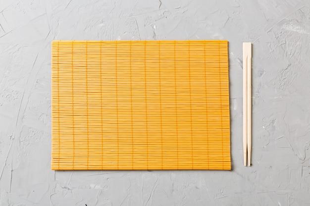 Due bacchette sushi con stuoia di bambù vuoto o piatto di legno su sfondo di pietra vista dall'alto con copia stace Foto Premium