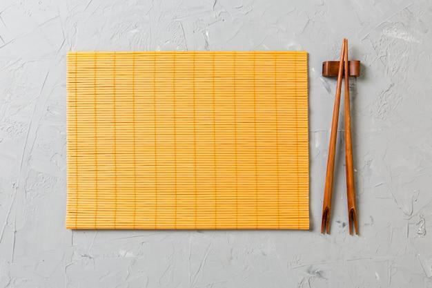 Due bacchette sushi con tappetino di bambù vuoto Foto Premium