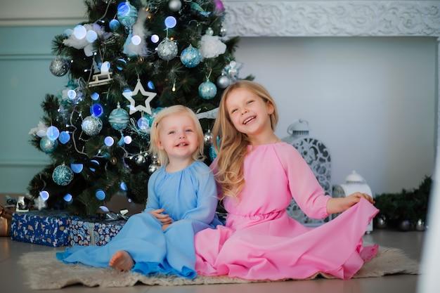 Due bambine accanto all'albero di natale Foto Premium
