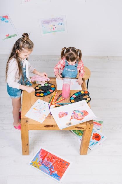 Due bambine che dipingono con aquarelle su carta al tavolo Foto Gratuite