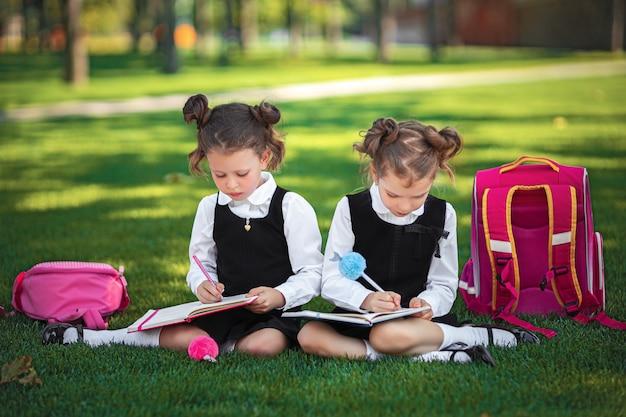Due bambine con zaino rosa seduto sull'erba dopo le lezioni e letto libri o lezioni di studio, Foto Premium