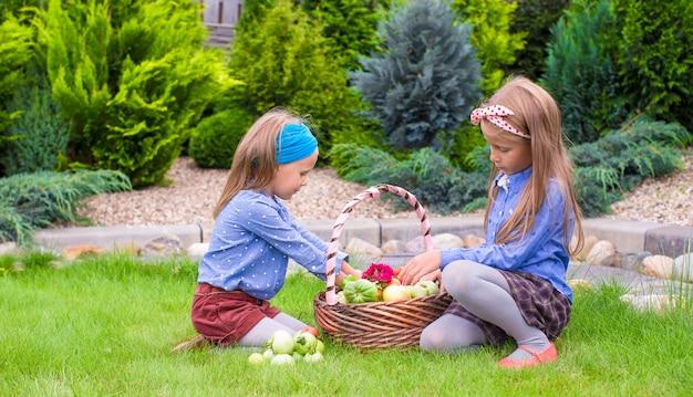 Due bambine felici con un grande raccolto autunnale di pomodori nei cestini Foto Premium