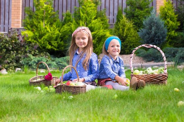 Due bambine felici con un grande raccolto autunnale di pomodori Foto Premium