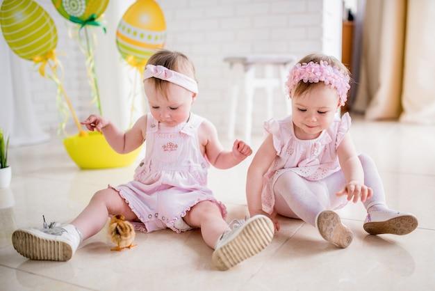 Due bambine in abiti rosa giocano sul pavimento in studio con decorazioni pasquali Foto Gratuite