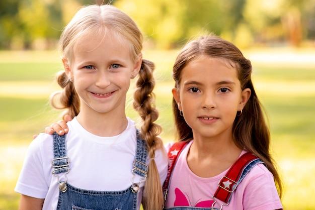 Due bambine sveglie che sorridono alla macchina fotografica Foto Gratuite