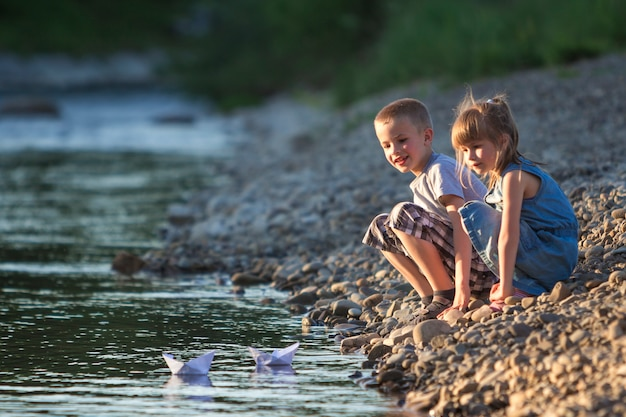 Due bambini che inviano barche di carta bianca sull'acqua. Foto Premium