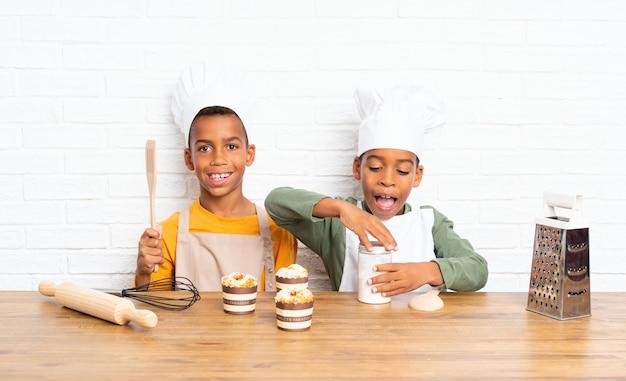 Due bambini fratelli afroamericani vestiti da chef Foto Premium