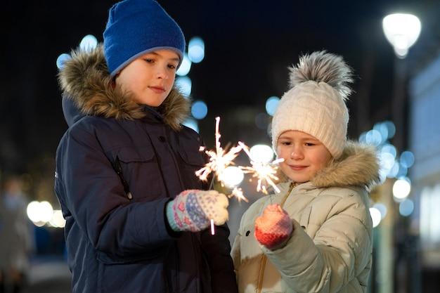 Due bambini in giovane età, ragazzo e ragazza svegli in vestiti caldi di inverno che tengono i fuochi d'artificio brucianti della stella filante nella notte scura all'aperto. concetto di celebrazione di natale e capodanno. Foto Premium