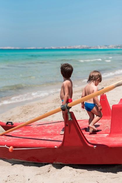 Due bambini in spiaggia in piedi sulla barca a remi Foto Gratuite