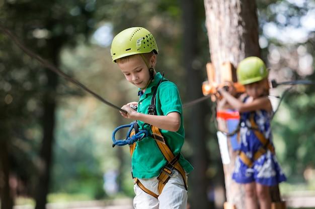 Due bambini, ragazzo e ragazza in imbracatura protettiva e caschi di sicurezza all'attività di arrampicata sulla via della corda. Foto Premium