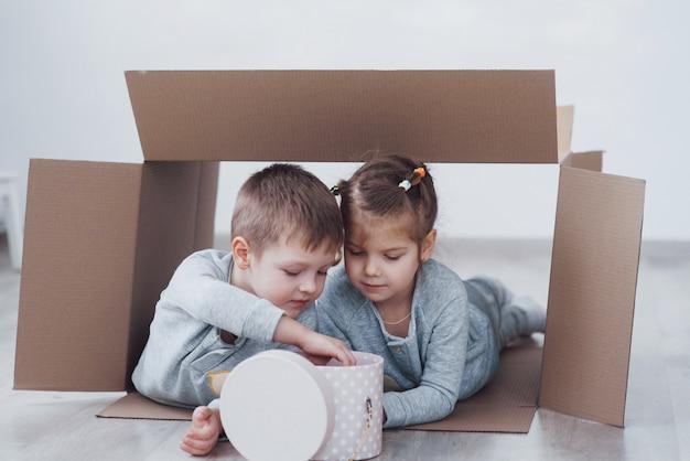 Due bambini un ragazzo e una ragazza che giocano in scatole di cartone. foto di concetto. i bambini si divertono Foto Premium