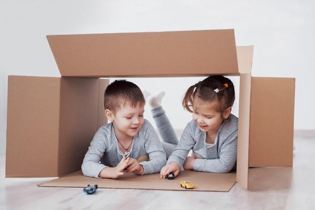 Due bambini un ragazzo e una ragazza che giocano le piccole automobili in scatole di cartone. foto. i bambini si divertono. foto di concetto. i bambini si divertono Foto Premium