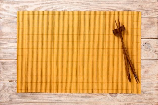 Due bastoncini di sushi con piatto di legno giallo vuoto bambù opaco su sfondo marrone in legno vista dall'alto con spazio di copia. sfondo vuoto cibo asiatico Foto Premium