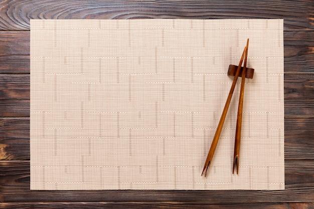 Due bastoncini di sushi con stuoia di bambù marrone vuota o piastra di legno su legno Foto Premium